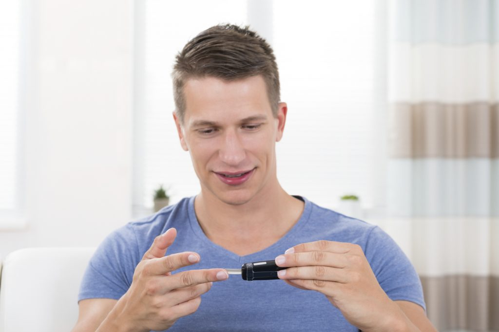 Close-up Of Young Happy Man Checking Blood Sugar Level With Glucometer