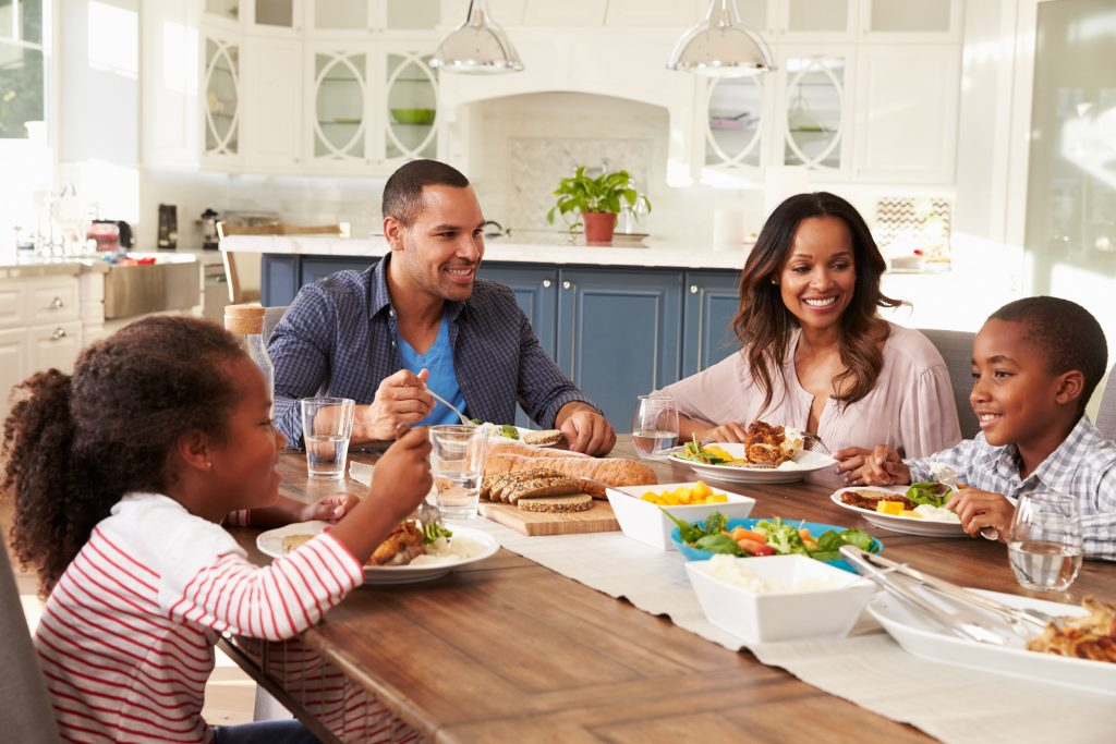 Parents and their two children eating at kitchen table