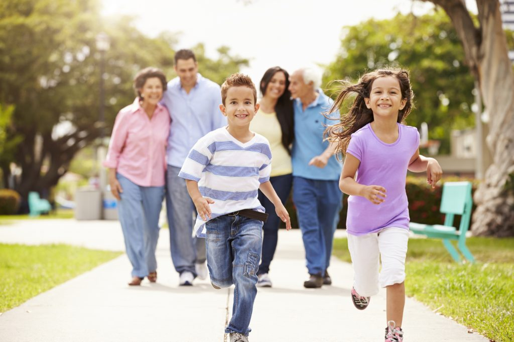 Multi Generation Family Walking In Park Together Children Running Ahead